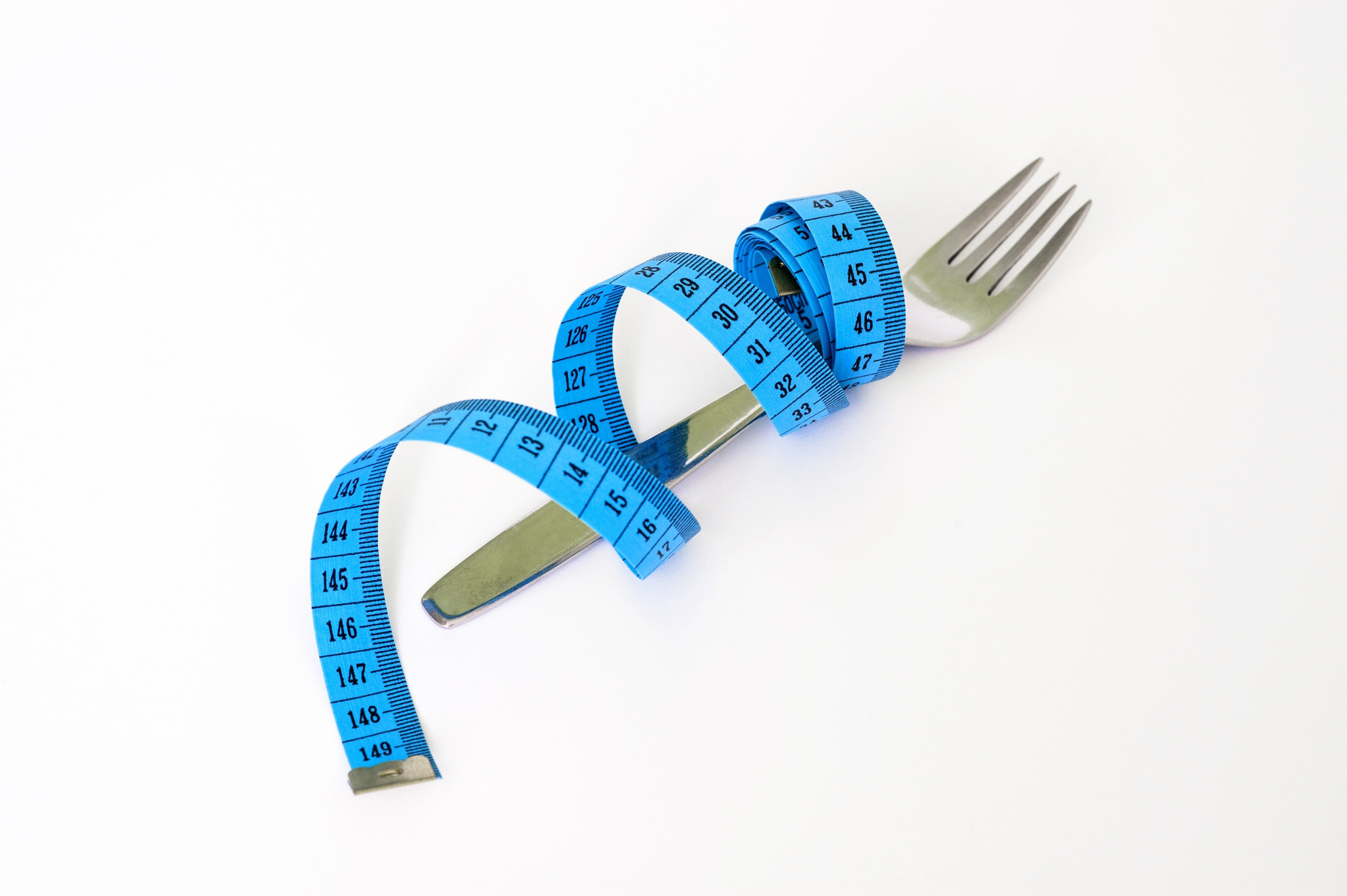 fork and measuring tape to depict an eating disorder
